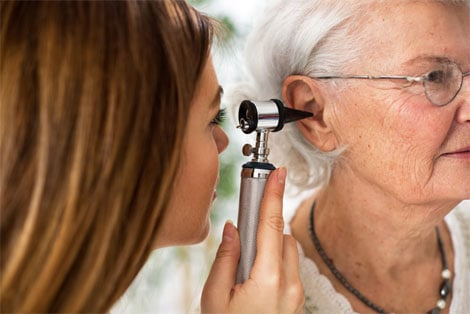 Doctor examining patient ear with otoscope