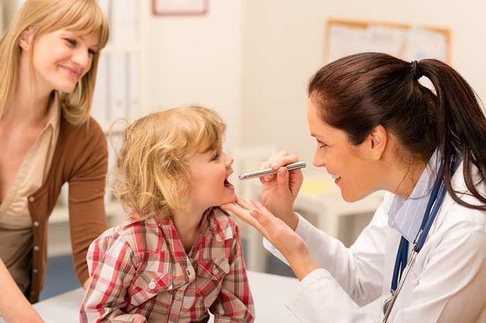 Doctor checking child eyes with penlight
