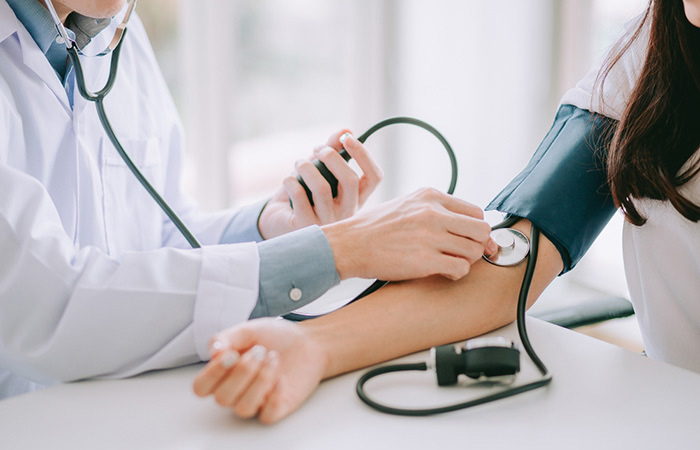 Doctor monitoring patient blood pressure with stethoscope and blood pressure cuff