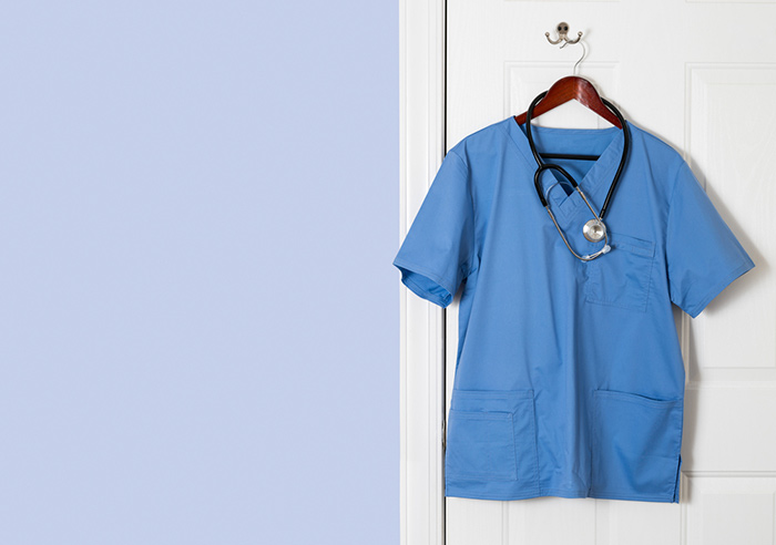 Mens blue scrub top hanging on door with stethoscope
