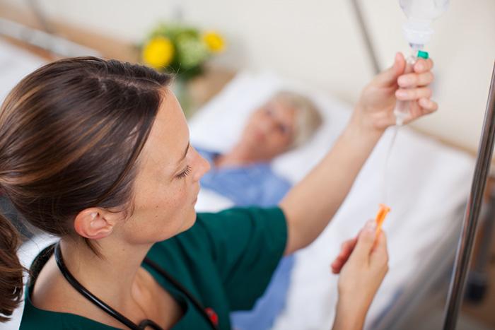 Registered nurse adjusts IV infusion