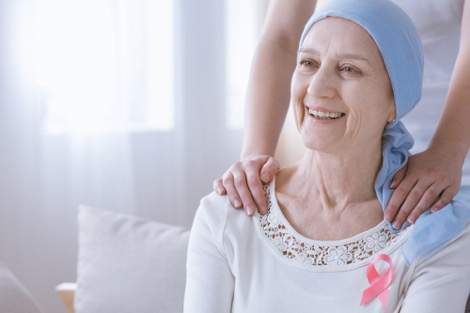 Patient wearing white shirt and awareness ribbon