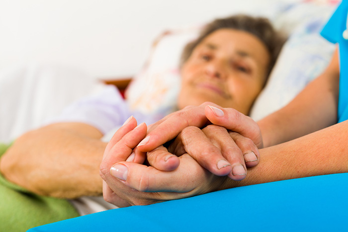 Caregiver holding elderly patient hand