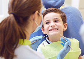 dental hygienist examining child at dentist office
