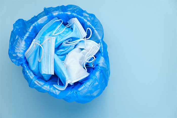 discarded surgical masks in the trash