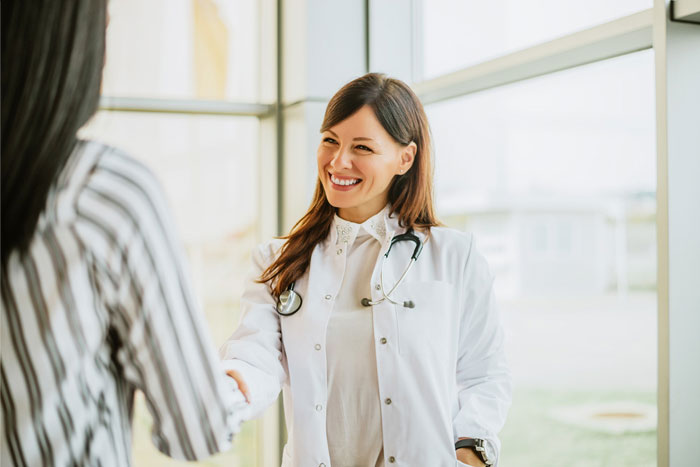 smiling female doctor smiles greets medical sales rep