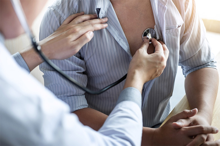 Doctor uses stethoscope to listen to patient chest sounds