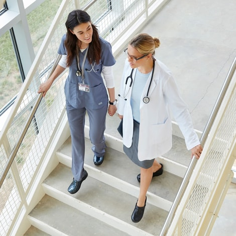 Doctor and nurse walk down stairs wearing Danskos