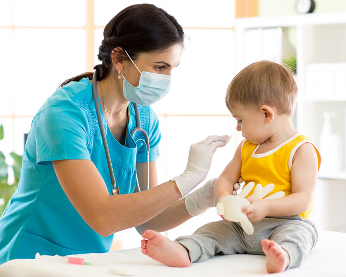 pediatric doctor preparing baby for vaccination