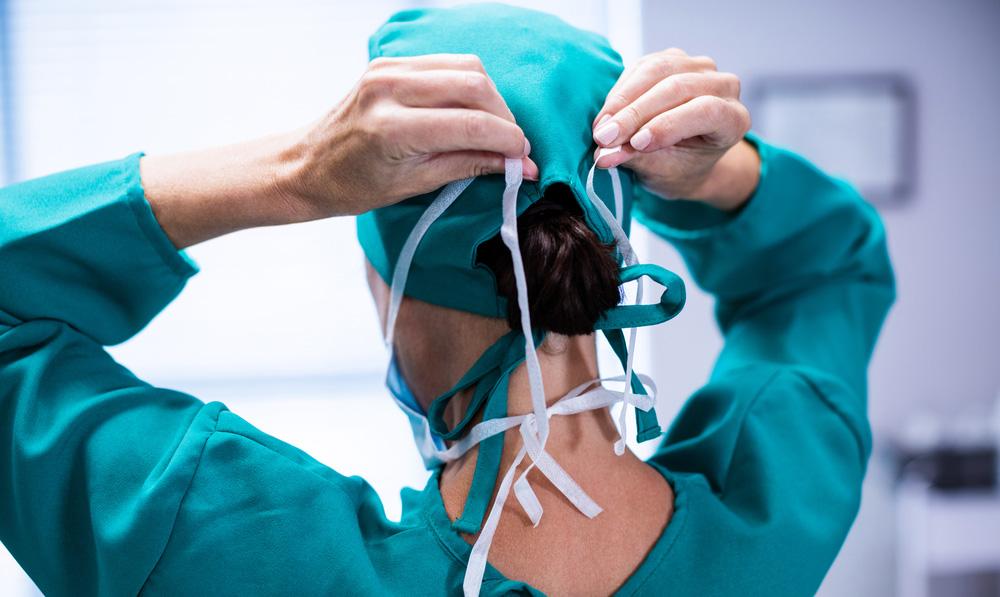 Doctor wearing ponytail scrub cap ties surgical mask