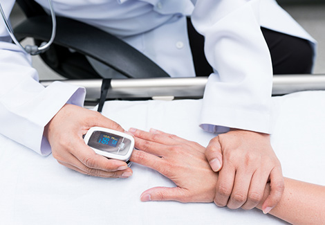 Doctor using an electronic pulse oximeter on a patient