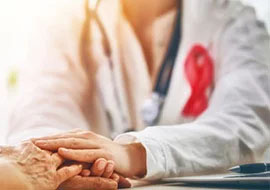 Doctor wearing red awareness ribbon touching patient's hand