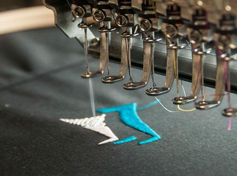 Embroidery machine adding embroidered logo to custom scrubs