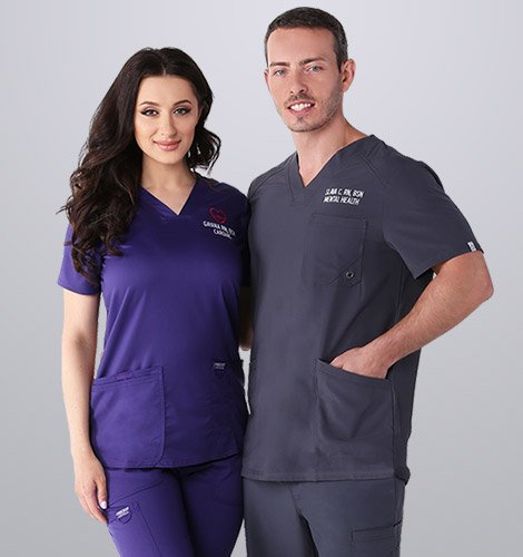 Female and male nurse standing together wearing Cherokee scrubs in purple and dark gray