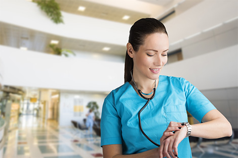 Female nurse checking wristwatch for the time