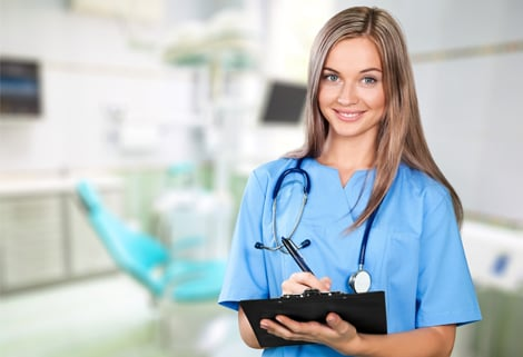 Female nurse smiling while holding clipboard