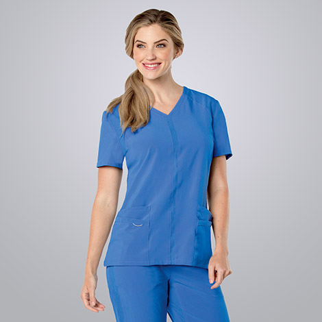 Female nurse wearing blue Landau scrubs against a white background