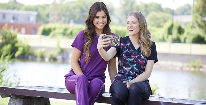 Female nurses in stylish scrubs taking a photo