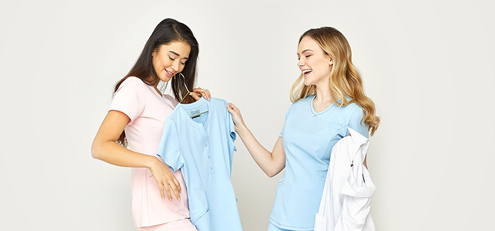 Two female nurses trying on colorful scrubs
