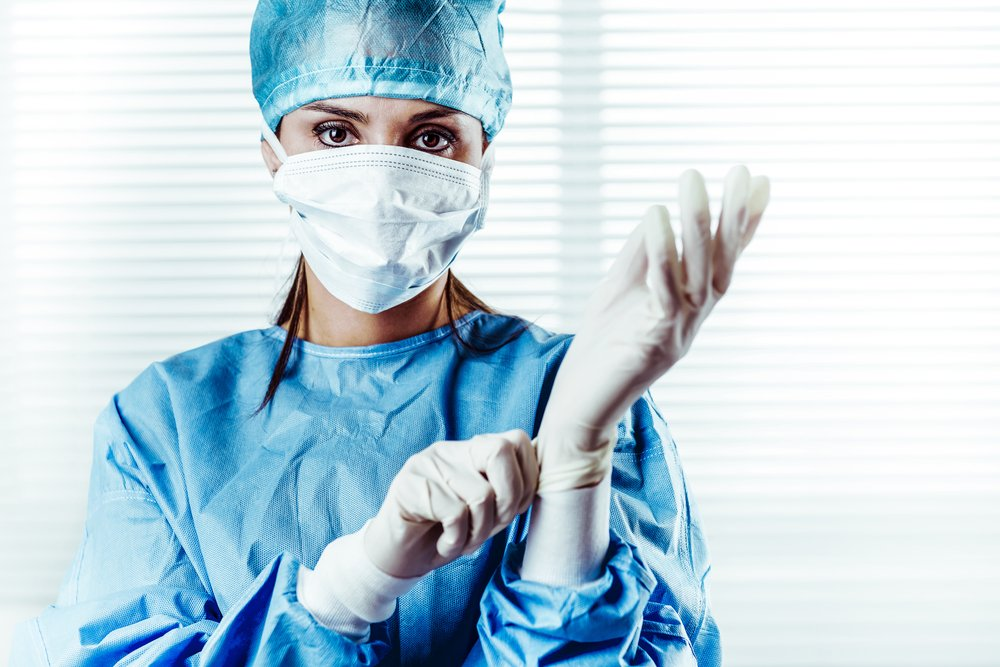 Female surgeon putting on surgical exam gloves