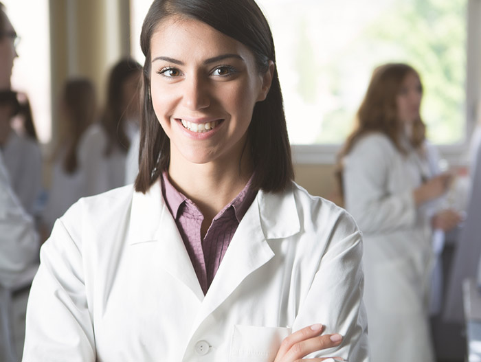 Female medical student wears white coat during ceremony