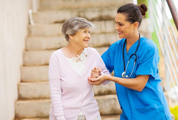 geriatric nurse helping elderly patient