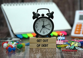 alarm clock and wooden blocks that say get out of debt