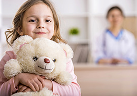 Girl hugs bear in doctors waiting room