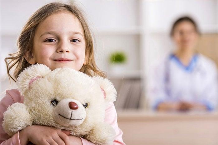 Girl hugs bear in doctors waiting room