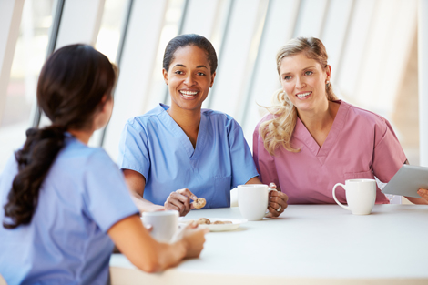 Group of female nurses talking together at table
