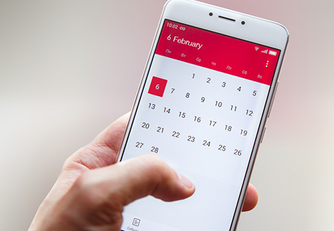 Hand holding a smartphone with a calendar app