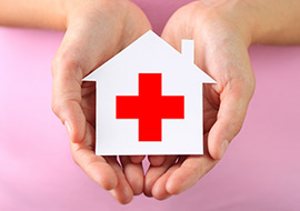 Woman's hands holding a white paper house with the Red Cross symbol