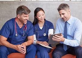 three healthcare workers sitting together using tablet