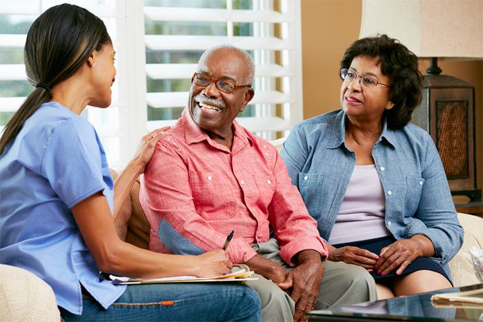 home healthcare nurse discusses treatment plan with elderly patients