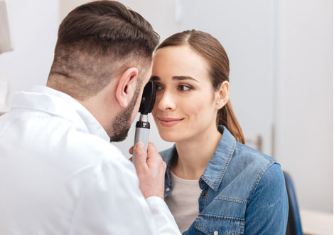 Male doctor using ophthalmoscope to examine a female patient's eye