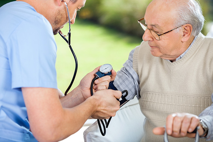 Male home health aide measuring senior patient's blood pressure