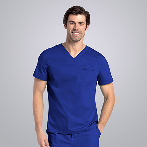 Male nurse smiling and wearing blue Landau scrubs