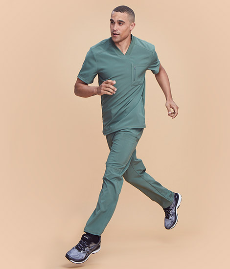 Male nurse running and wearing green Infinity by Cherokee scrubs