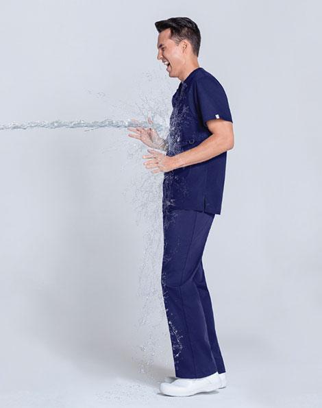 Male nurse wearing blue scrubs standing in hospital room