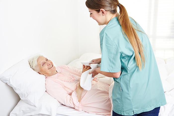 Medical assistant bathes female patient