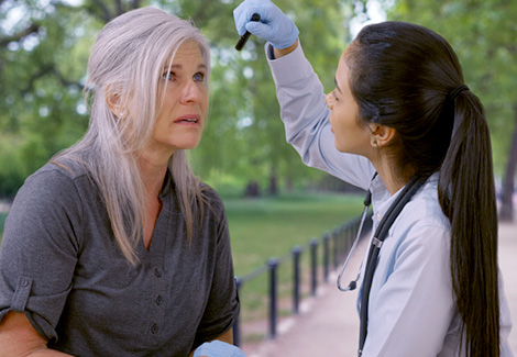 Female medical professional checking vitals of an elderly woman in a park