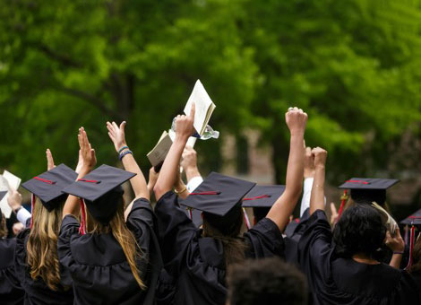 Medical school graduates celebrating in cap and gown at graduation ceremony