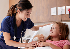 pediatric nurse checking on young patient in bed