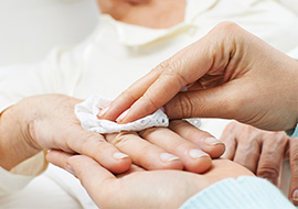 Nurse cleans patient hand