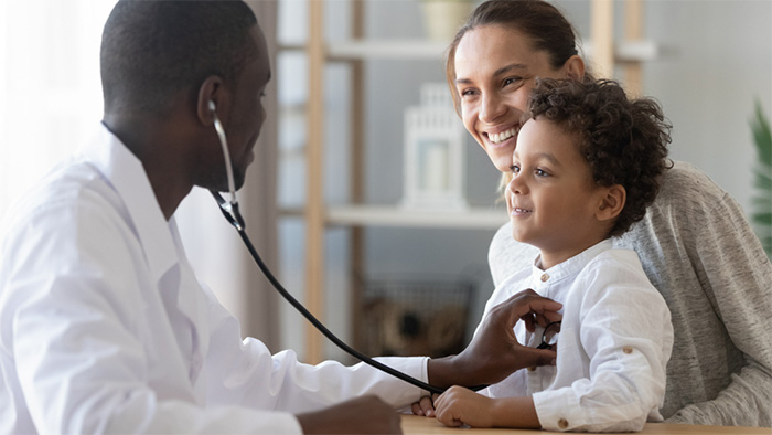 nurse practitioner examining young patient with stethoscope