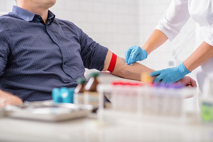 nurse preparing patient arm for drawing blood