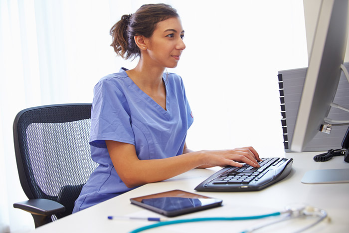 female nurse typing on office computer