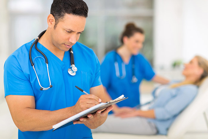 medical professional writing on a clipboard with patient in background