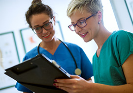 two nurses in scrubs looking over paperwork