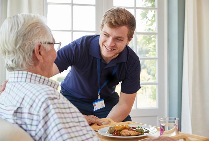 nursing assistant serving dinner to senior patient